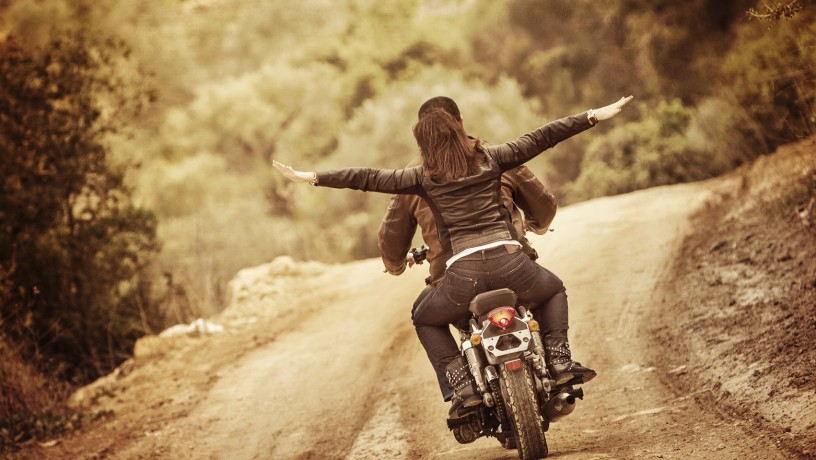 Sporty family traveling on motorbike, riding on motorcycle with raised up hands, active people, extreme sport, freedom concept